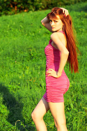 Young beautiful redhead woman standing on a green grass Stock Photo