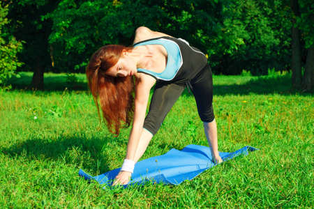 Young woman doing yoga exercise on green park Stock Photo - 12650421