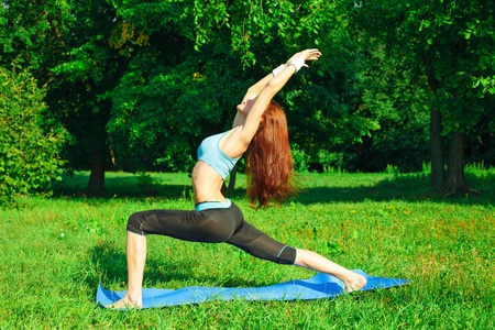Young woman doing yoga exercise on green park Stock Photo