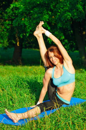 beautiful redhead: Young woman doing yoga exercise on green park Stock Photo