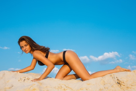 Beautiful young woman posing on sand photo