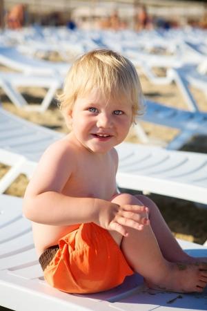 Cute little boy seduto sul salotto sulla spiaggia