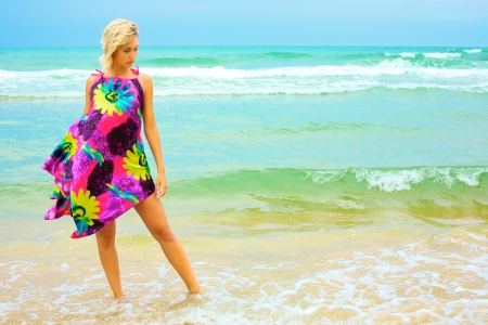 Young blonde woman in dress on beach photo