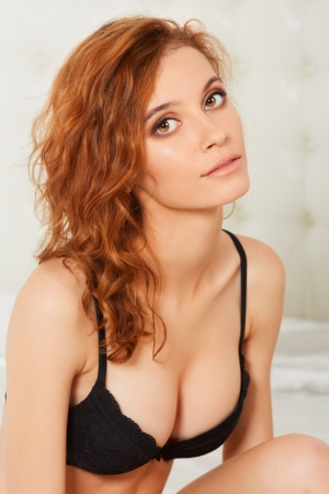 Beautiful young redheaded woman in bed
