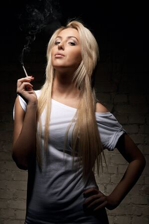 Portrait of young blonde woman with a cigarette on dark background photo