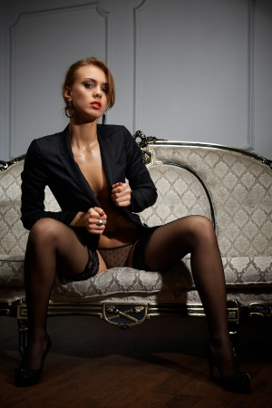Young woman in black lingerie sitting on the couch Stock Photo - 17480778
