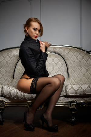 erotic dress: Young woman in black lingerie sitting on the couch Stock Photo