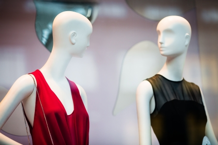 window display: Two woman mannequins in red and black dresses in shopping window in store  selective DOF