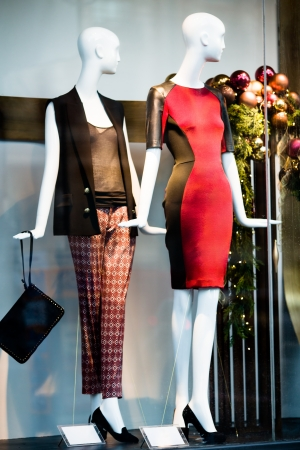 Two woman mannequins in red and black dresses in shopping window in store  selective DOF