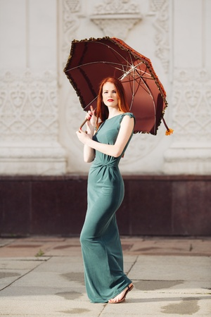 Portrait of beautiful red-haired young woman with umbrella photo