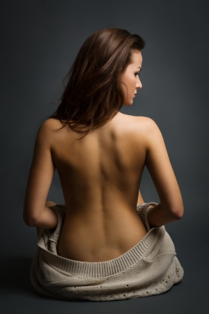 Young beautiful sexy woman, back view, sitting on а floor photo