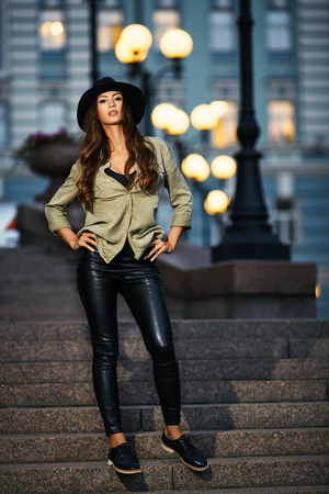 street night: Full length portrait of attractive elegant young woman with black hat standing on the stair, street fashion Stock Photo