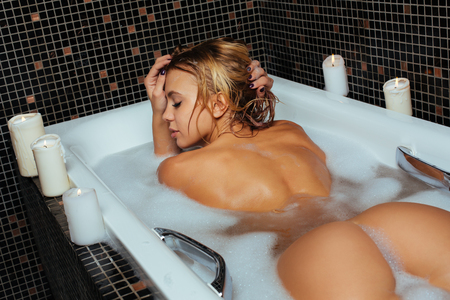 Beautiful young blonde woman in a bath