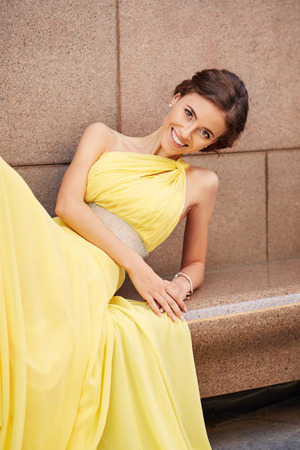 granite wall: Outdoor portrait of young beautiful woman fashion model in yellow dress on granite wall background