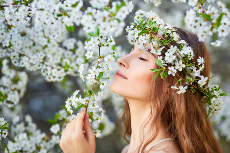 circlet: Young beautiful woman in circlet of flowers enjoying smell of blooming tree on a sunny day. Close eyes Stock Photo
