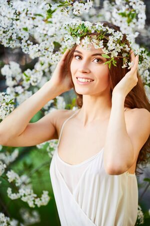 circlet: Young beautiful woman in white dress in circlet of flowers