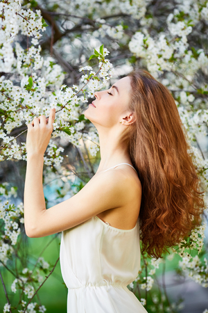 Young beautiful woman in circlet of flowers enjoying smell of blooming tree on a sunny day. Close eyes Stock Photo