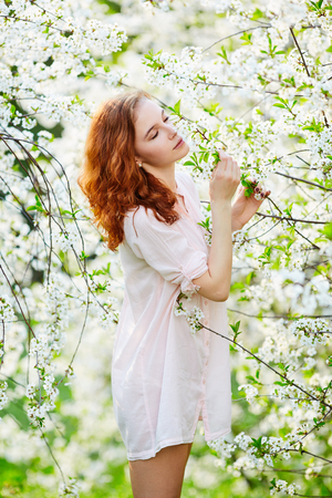Young beautiful woman enjoying smell of blooming tree on a sunny day (selective DOF) Stock Photo