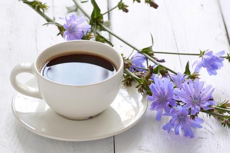 Taza de bebida de achicoria de té de café con flor de achicoria en una mesa blanca Foto de archivo - 85106872