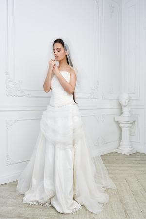 スリムな美しい若い女性がスタジオでウェディング ドレスでポーズ 写真素材