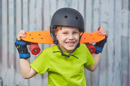 skateboarder: Boy in helmet posing with skateboard