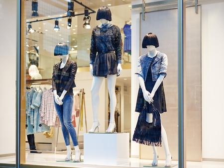 De ledenpoppen die zich in vertoning van het opslagvenster bevinden van de toevallige kledingswinkel van vrouwen in winkelcomplex Stockfoto - 90369417
