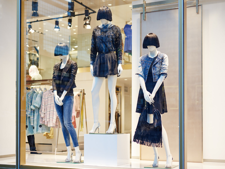 Mannequins standing in store window display of women s casual clothing shop in shopping mall Reklamní fotografie