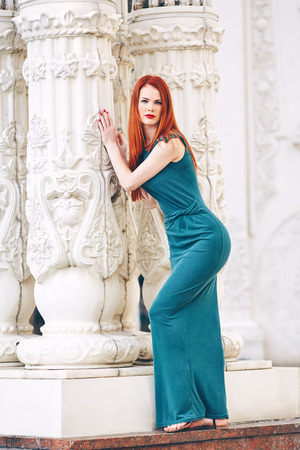 Portrait of a beautiful red-haired young woman in a green dress next to a column