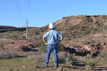 worker standing in front of mountain 版權商用圖片