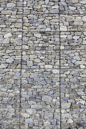 Natural stone background texture, detail of a wall decorated with natural stone, textured background Banco de Imagens