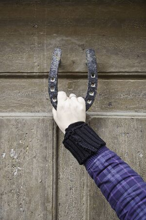 doorknocker: Woman holding the bridle, detail of a young woman holding the shoe in an old wooden door Stock Photo