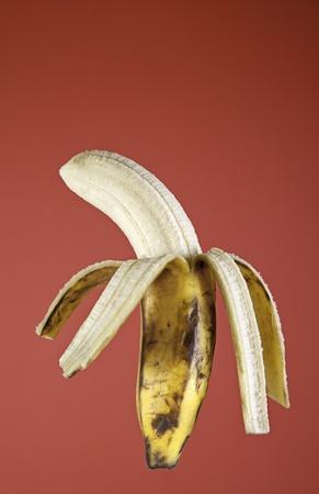Banana peel, peeled tropical fruit detail on red background photo