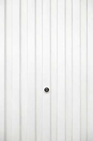 peephole: White metal door, detail of a metal door painted white, peephole, real protection and safety