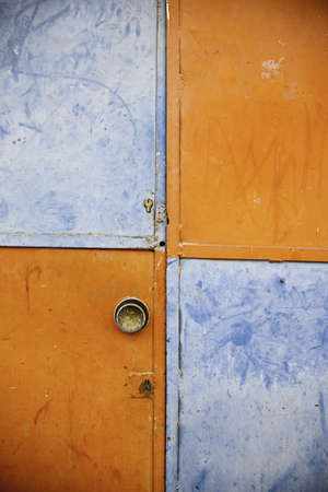 abandonment: Orange and blue closed door, detail of a decorated door in the city, loneliness and abandonment Stock Photo