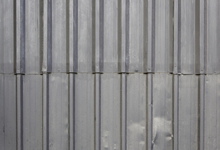 sustained: Abandoned metal wall, detail of a dented metal wall and disused