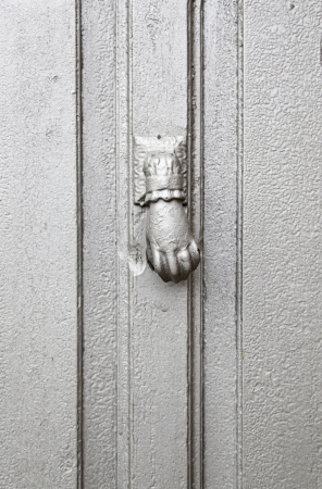 caller: Caller silver at the door, detail of a wooden door painted silver in the city background Stock Photo