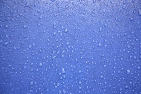 shiny car: Water druppels op blauwe, detail van een natte blauwe oppervlakte water, regen in de stad