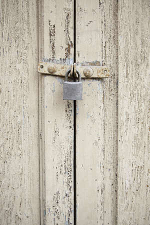 Closed wooden door, detail of an old wooden door locked with a padlock photo