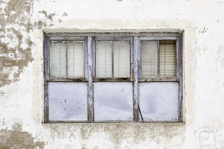 Old abandoned window, detail of a window of a house in ruins, evictions and abandonment, crisis   Stock Photo