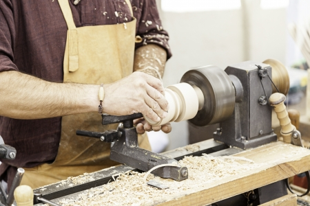 Carpenter Woodworking, detail of a worker with a lathe, shaping wood