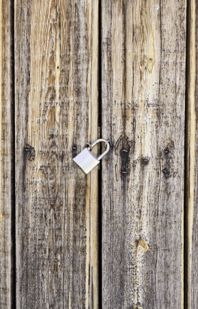 Wooden door locked with a padlock, detail of a textured, protection photo