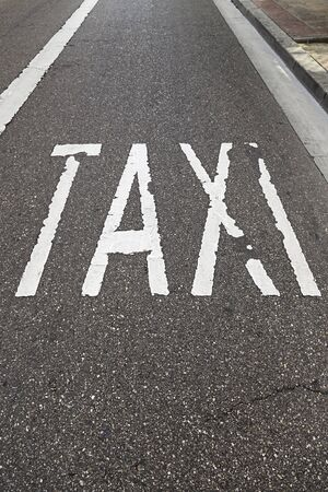 Taxi sign on the road, detail of a text signal in soil, urban transport photo