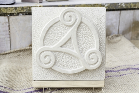 Trisquel carved in stone, detail of a Celtic symbol carved by hand in an old stone, traditional crafts, art Stock Photo