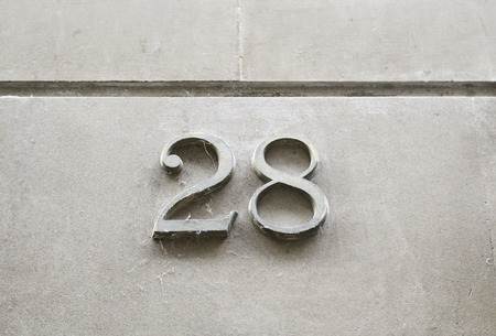 honouring: Number twenty-eight on the wall, detail of a number of information on a street, numbers
