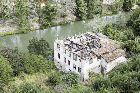 Old house in ruins, detail of a ruined house next to a river, neglect photo