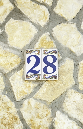 Number twenty-eighth in a stone wall, detail information about numbers on the street photo