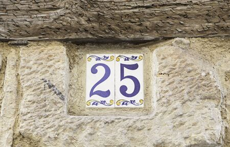 thread count: Number twentyfive on a wall, detail of a number of information on a wall in the city