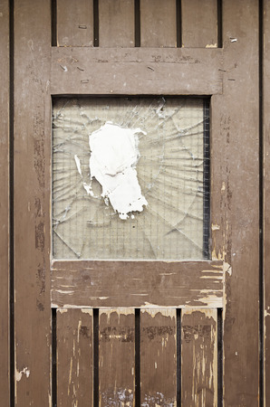 Old broken door, detail of a door with a broken glass, and drop protection photo