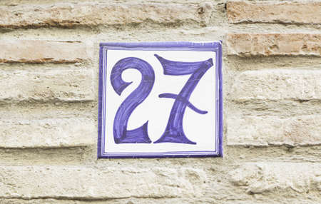 honouring: Number twenty-seven on a wall, cipher text in a wall of a house, information numbers