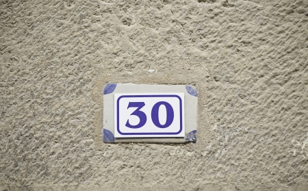 Number thirty on a wall, detail of a number of information in a house photo